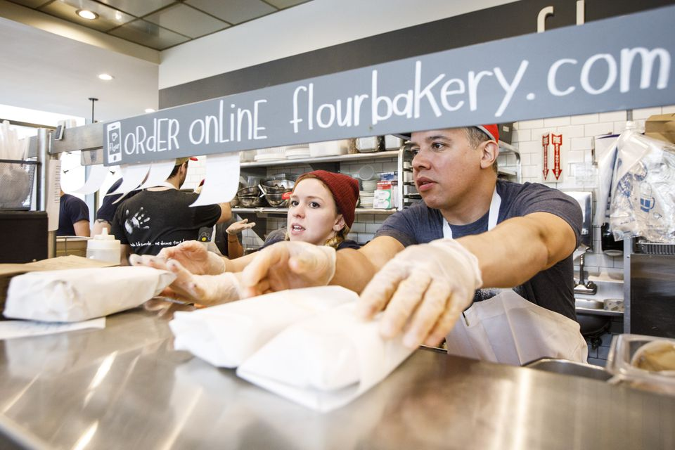 Kitchen staffers delivered food orders to the counter at Flour Bakery in Boston, an establishment that takes online orders as well as in-person ones.
