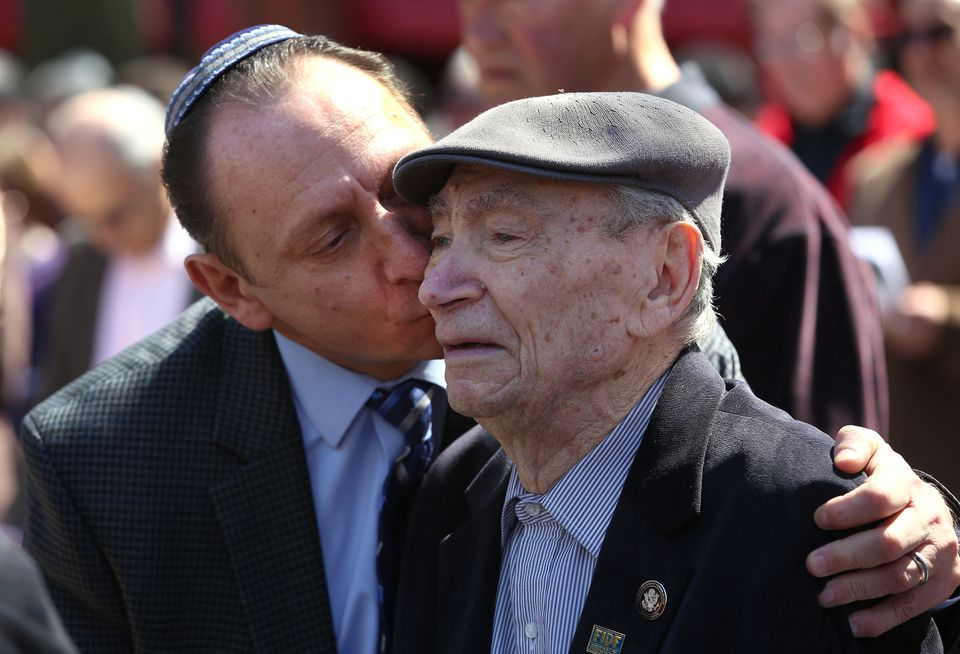 At an outdoor gathering Sunday, Mark Rogozinski leaned over to kiss his 91-year-old father, Abram Rogozinski, who is a survivor of seven camps.