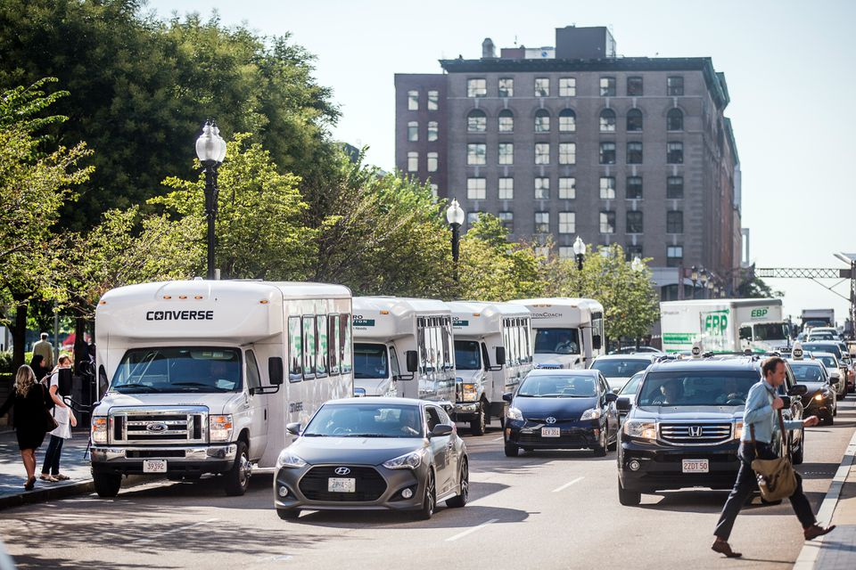 A few private shuttles waited for riders on Summer Street in Boston. The Massachusetts Convention Center Authority has a plan for shuttles.