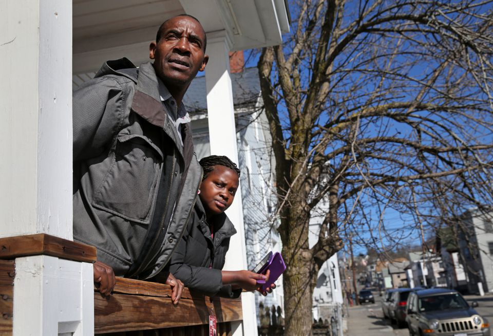 Sendegeya Bayavuge, left, and his daughter Maria Uwimana, 17, looked for the school bus while waiting for his other children to arrive at their home in Lowell.