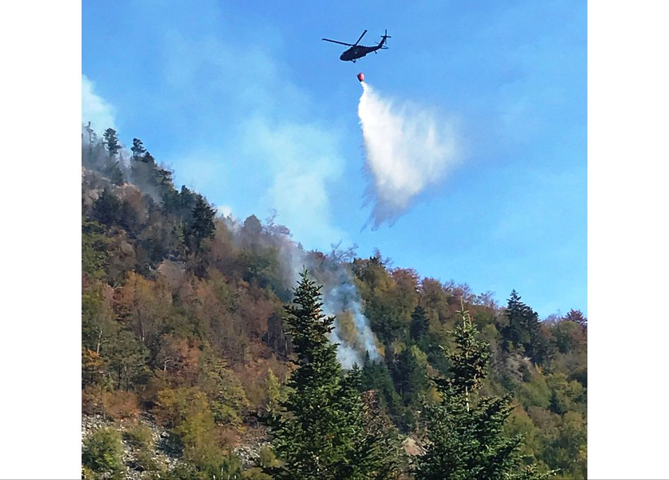 A helicopter worked to suppress a forest fire in the White Mountains in Woodstock. N.H.