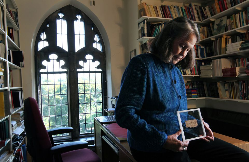 Karen L. King, Hollis Professor of Divinity at Harvard University, in her office with the papyrus fragment in question.