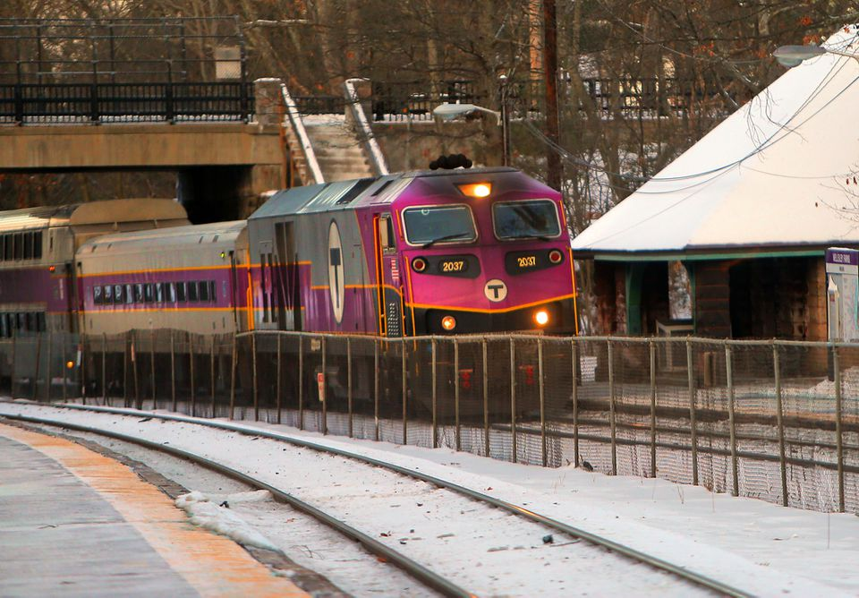 An outbound MBTA commuter rail train drops off passengers at the Wellesley Farms stop.