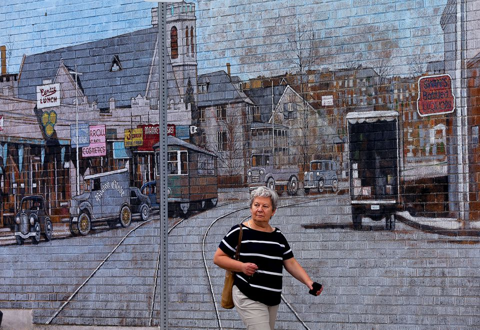 A woman walked past a mural depicting and old view of Centre Street on May 26.
