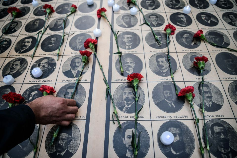 People lay red carnations on pictures of Armenian intellectuals, detained and deported in 1915, during a rally to commemorate the 101th anniversary of the 1915 mass killing of Armenians in the Ottoman Empire.