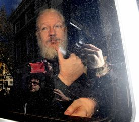 Julian Assange gestured as he arrived at Westminster Magistrates' Court in London, after the WikiLeaks founder was arrested by officers from the Metropolitan Police and taken into custody Thursday.