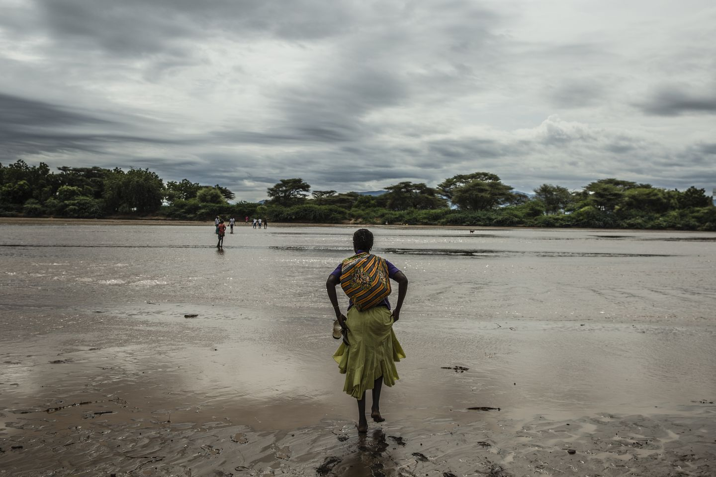 A woman hitches up her skirt to cross the Tarach River at the UNHCR refugee camp .