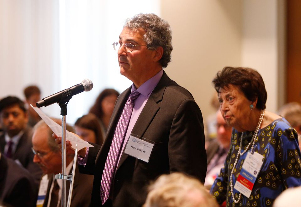 """Dr. Roger Kligler, who has metastatic prostate cancer, spoke to the Massachusetts Medical Society in support of what he calls """"medical aid in dying."""" Standing behind him waiting to speak was Dr. Barbara Rockett, a former two-time president of the medical society who opposes this end-of-life option and calls it """"physician-assisted suicide."""""""