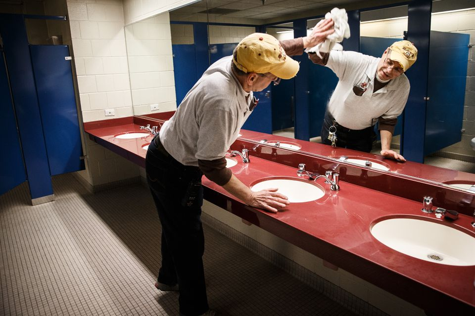 Fred Vautour polished a mirror as he cleaned Boston College's Robsham Theater on Friday.