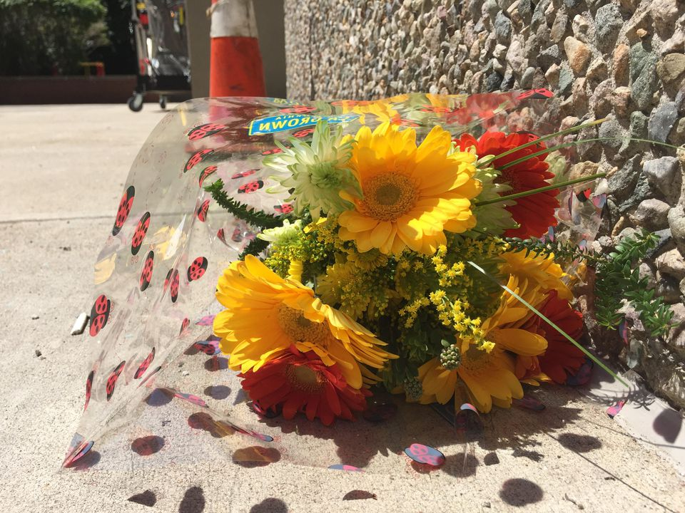 A neighbor left a bouquet of flowers near the spot where a 5-year-old girl fell from a fourth-floor window.