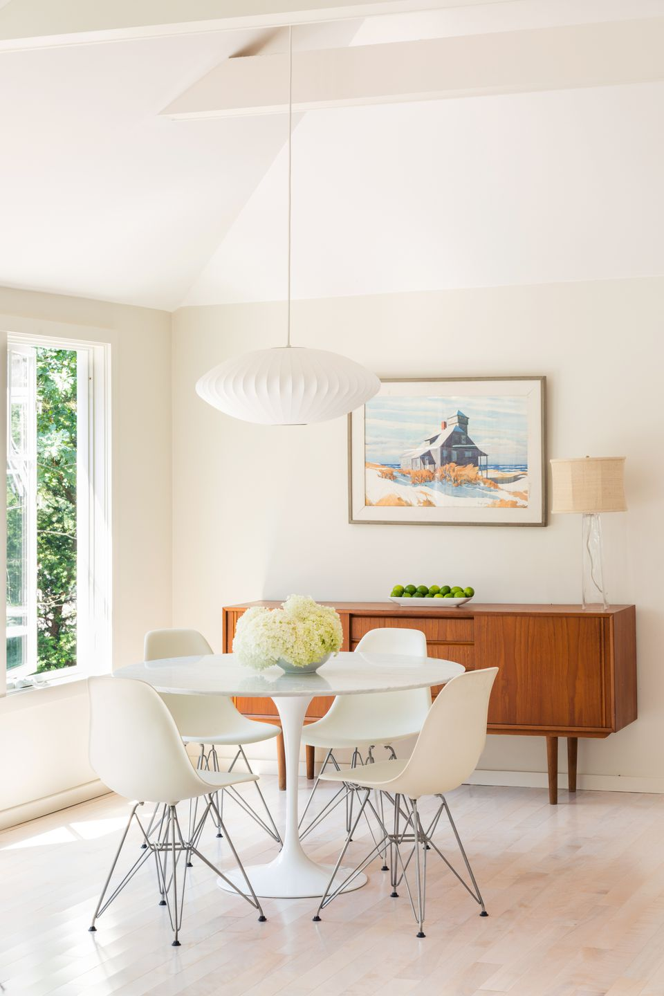 """Hovering over the Eero Saarinen dining table and Eames chairs, an iconic mid-century Nelson Saucer Bubble Pendant by Herman Miller is the only exposed light fixture in the main living area other than table lamps. """"All of the rest recede into the ceiling,"""" says Alison Alessi of A3 Architects."""
