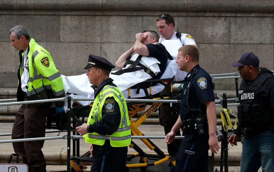 One of the officers left the main library in Copley Square on a stretcher. The injuries were not life-threatening, a spokeswoman said.