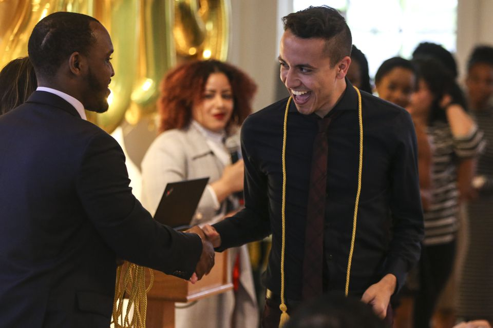Joel Pimentel Alves (right), 22, shook hands with Jared Smith, a student success adviser, at a Tufts ceremony on Friday.