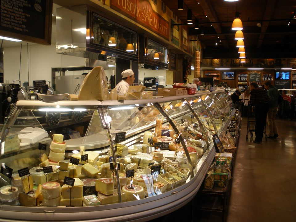Glass cases filled with Italian, French, and Spanish cheeses and deli meats