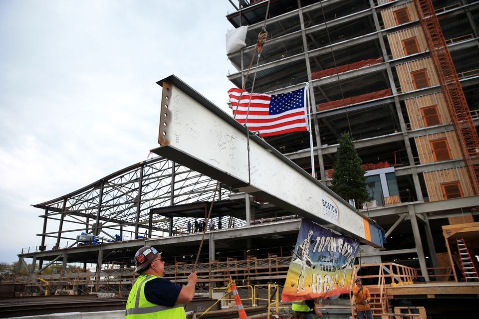 Jack Glavin, site forman for Prime Steel, helped guide a steel beam the topping-off ceremony at the new Warrior Ice Arena at Boston Landing.