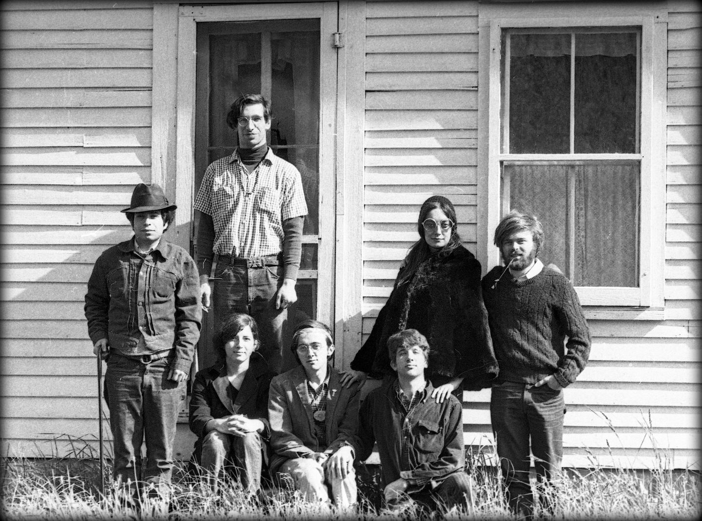 The pioneers of Total Loss Farm pose on the doorstep of the farmhouse. Sitting, from left: Michelle Clarke, Ray Mungo, and Peter Simon. Standing, from left: Richard Wizansky, Marty Jezer, Verandah Porche,  and Laurie Miller.