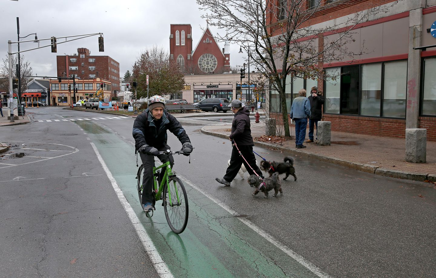 A dog walker crossed the street as a cyclists rode through Union Square.