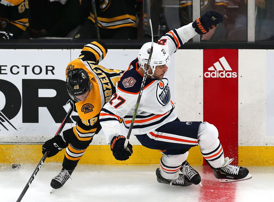 The Bruins' Matt Grzelcyk collides with the Oilers' Milan Lucic against the boards in the first period of Thursday's game.