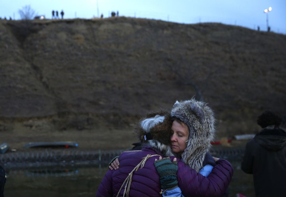 Protesters embraced as police stood on a hilltop in Cannon Ball, N.D., near Standing Rock.