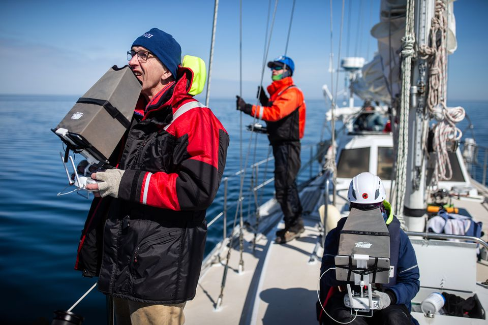 Michael Moore (left) and Carolyn Miller worked to collect whale data on Moore's sailboat Rosita in Cape Cod Bay.