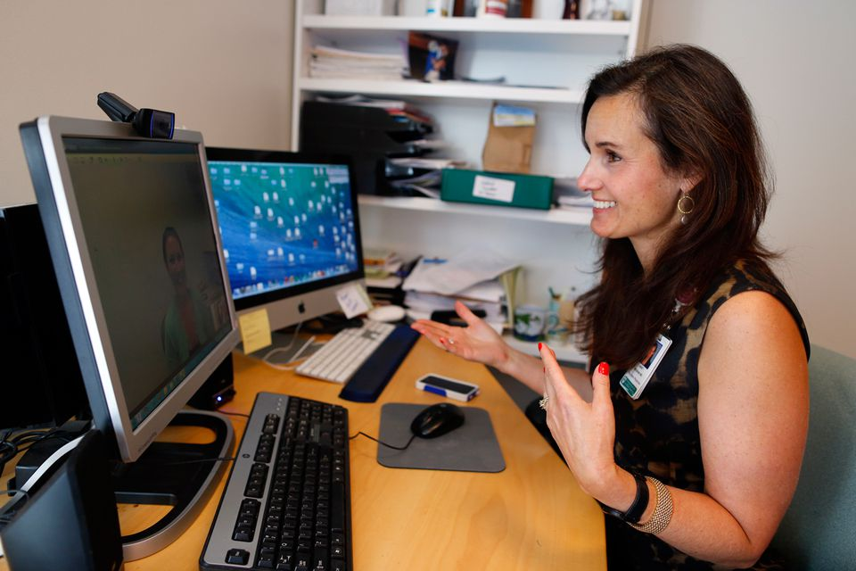 Janet Wozniak, associate director of the Bressler Program for Autism Spectrum Disorders, uses video-conferencing technology to talk with her patients and colleagues at her office at Massachusetts General Hospital.