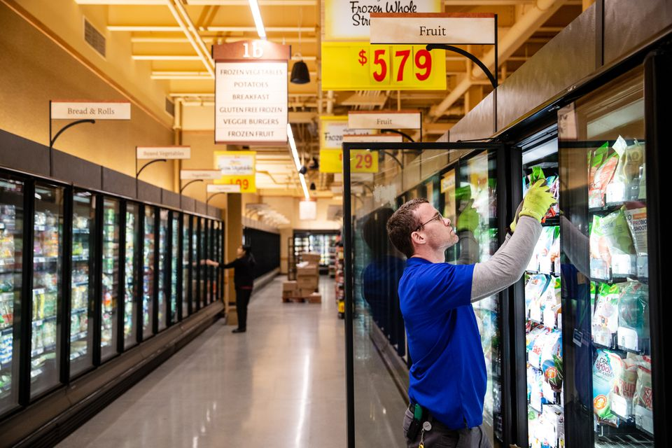 A worker stocked shelves in the frozen foods section at the new Wegmans in the Natick Mall.