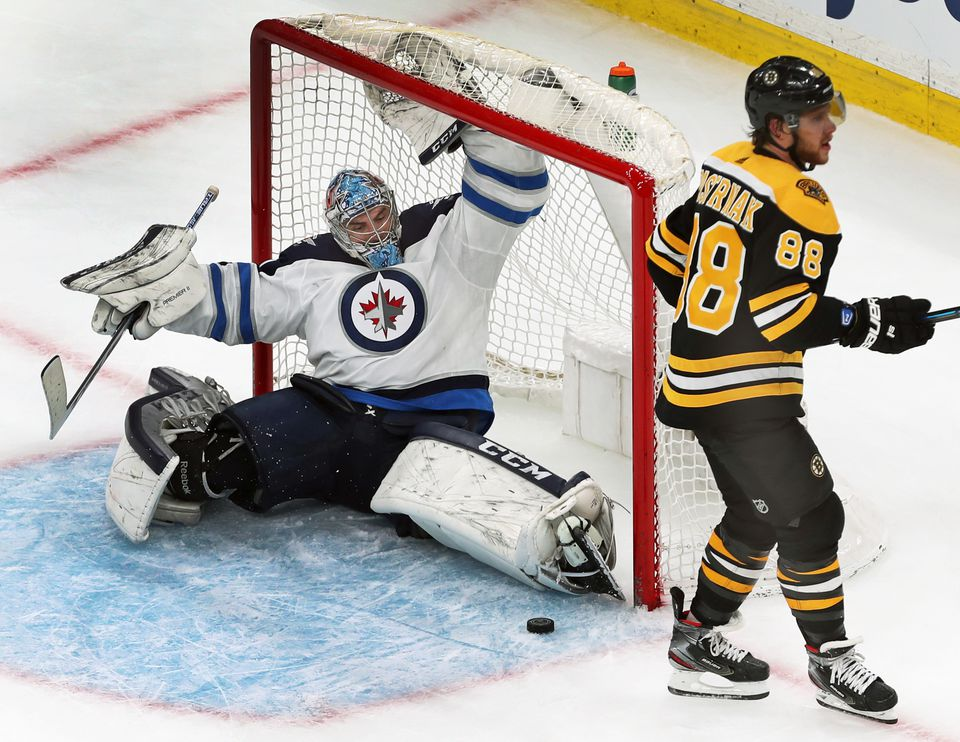 The Bruins' David Pastrnak (right) was stopped by a nice skate save by Jets goalie Connor Hellebuyck in the shootout.