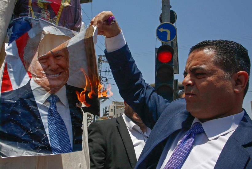On Monday a Palestinian protester in Halhul burned a photo of President Donald Trump during demonstrations against the upcoming US-led meeting in Bahrain on the Palestinian-Israeli conflict.