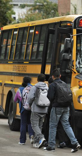 Students board school buses outside the Thomas Edison School in Brighton.