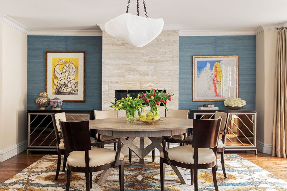 A piece by artist and onetime child prodigy Alexandra Nechita hangs to the left of the fireplace, and a Salvador Dali print the couple bought in Europe hangs to the right. A custom plastered chandelier by trans-LUXE floats above the room.