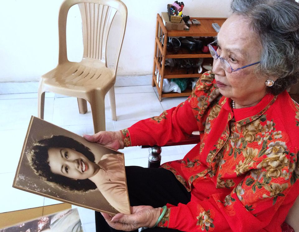 Mrs. Ngo, holding a picture of herself, was the most famous of North Vietnamese broadcasters during the Vietnam War.