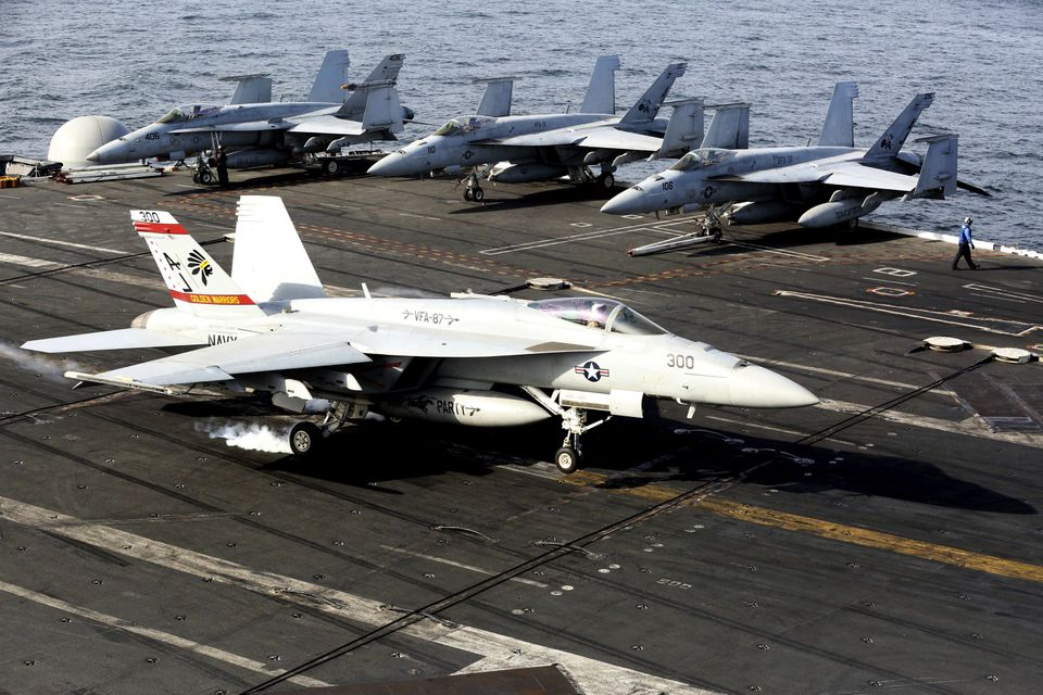 An F-18 fighter lands on the USS George H.W. Bush as it travels toward the Strait of Hormuz, on March 20, 2017.