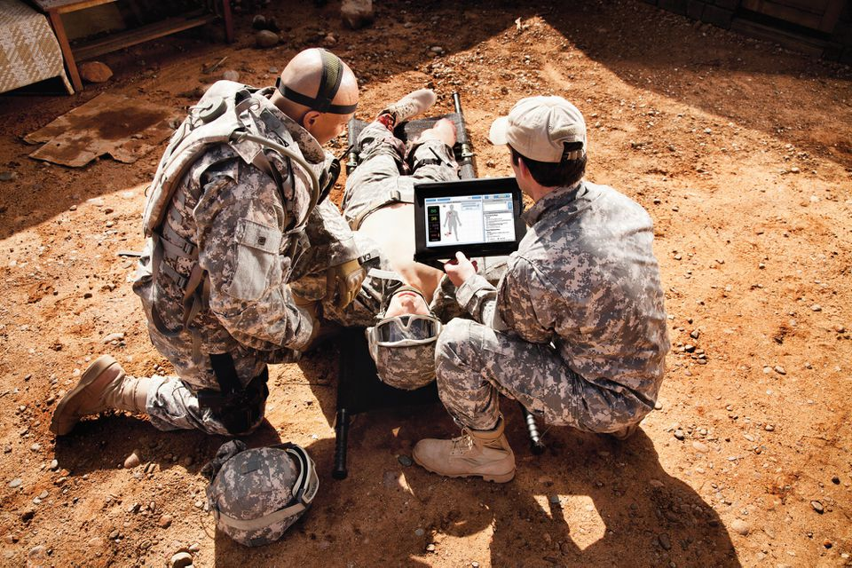 Military personnel worked on a casualty simulator that mimics a 190-pound man. The simulator was developed in part in Boston.