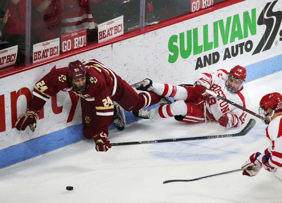 Boston College defenseman Kevin Lohan (left) battles with Boston University players for the puck during the first period of a game at Agganis Arena in December.