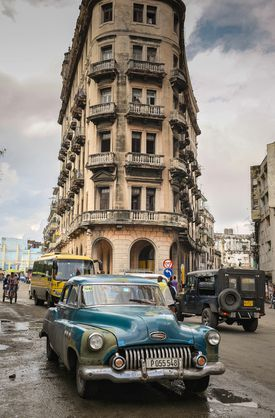 A vintage American car drives along a street in Havana in December.