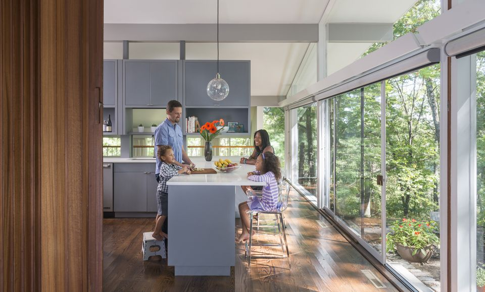 The Arneman family gathers around the L-shaped island, with Joanne and 6-year-old Eva perched on clear acrylic counter stools that help keep the narrow area in front of the glass sliders open and airy. Blue-gray cabinetry sets off the kitchen from the swaths of white surrounding it and also grounds the space, which floats in the middle of the house, extending to neither walls nor ceiling.  Upper cabinetry is supported by  two posts, eliminating the need for  a solid backsplash and allowing peekaboo glimpses of the dining area and the outdoors beyond.