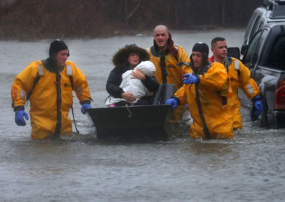 A mother and child are rescued by a boat from their home in Quincy on March 2.