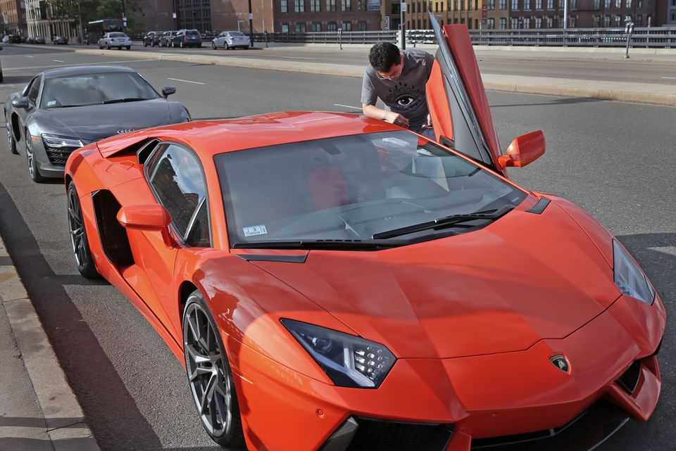 A student, who did not want to be identified, said he owns this orange Lamborghini and the Audi R8 Spyder behind it.