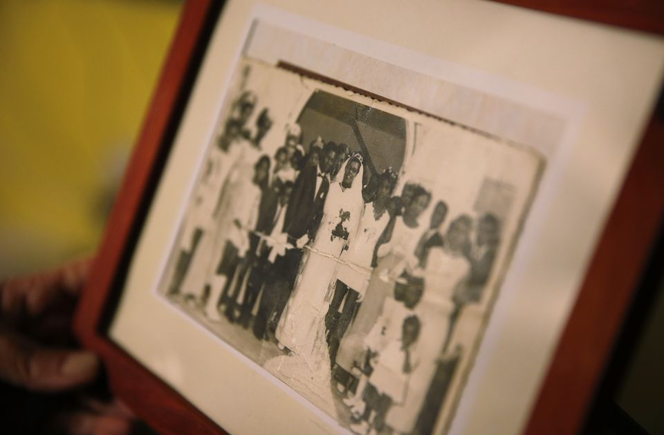 Marcelle Harrison holds a photo of her mother's wedding to her stepfather in Barbados that she keeps on display in the living room of her Cambridge home.
