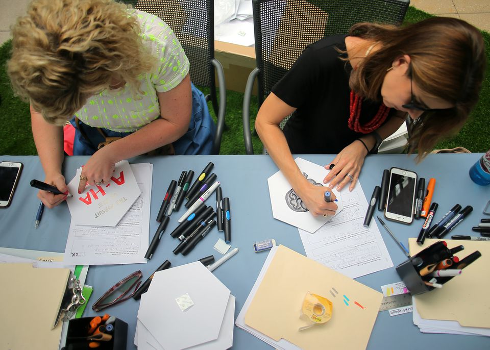 Graphic facilitators Erin King (left) and Tricia Walker drew illustrations based on survey questions for corporate client Abcam at an event in Kendall Square.