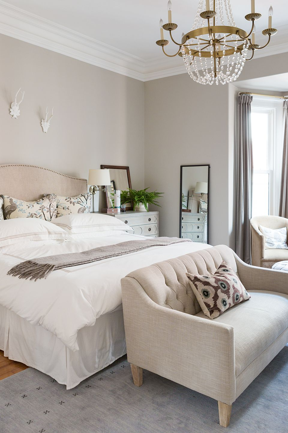 The transformation of the house began in the master bedroom, which the homeowners designated throughout the project as a sanctuary from the surrounding chaos. The small-scale settee is from Pottery Barn Kids.