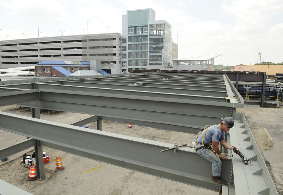 Iron worker Adam Chapman of Haverhill attaches bolts for a new plaza near Revere's Wonderland Station. A new $53.5 million MBTA garage looms behind him.