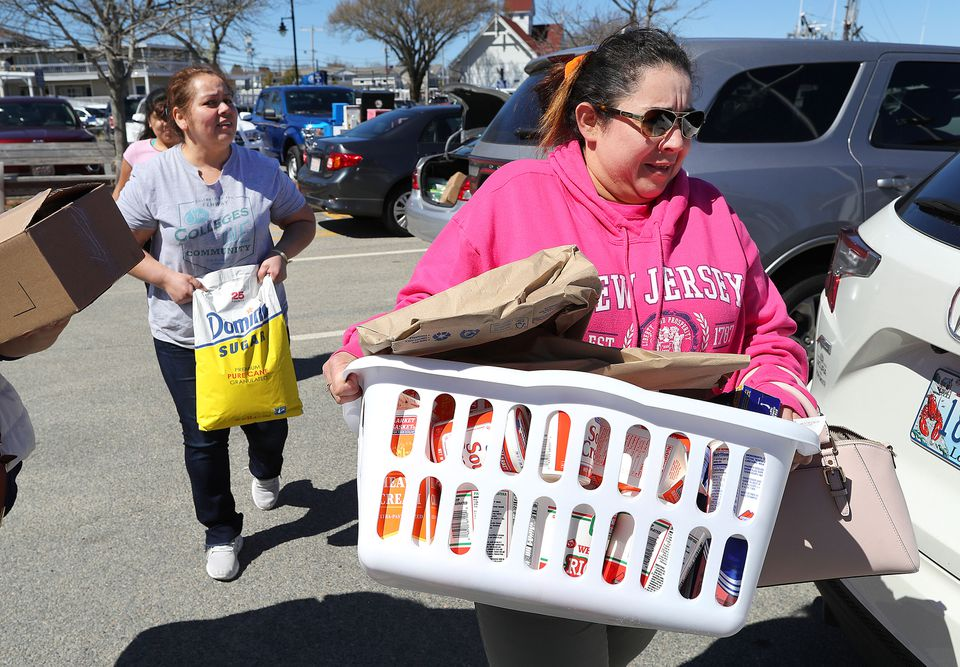 Rubidia Escobar carried a container filled with dairy products like milk, sour cream, and cottage cheese at the Hyannis Ferry Terminal parking lot. She is helped by her friend Ofelia Duarte (left) who unloaded a 25lb of sugar from Duarte's car after they went shopping at Market Basket in Bourne.