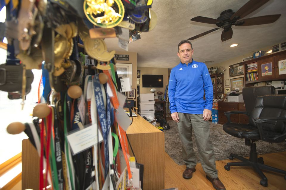 Boston Marathon race director Dave McGillivray's home office is filled with trophies and medals from some of his 145 marathons.
