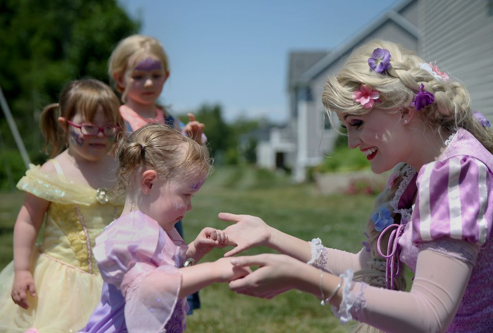 Busby holds hands with Emma Genest, 2, also dressed as Rapunzel.
