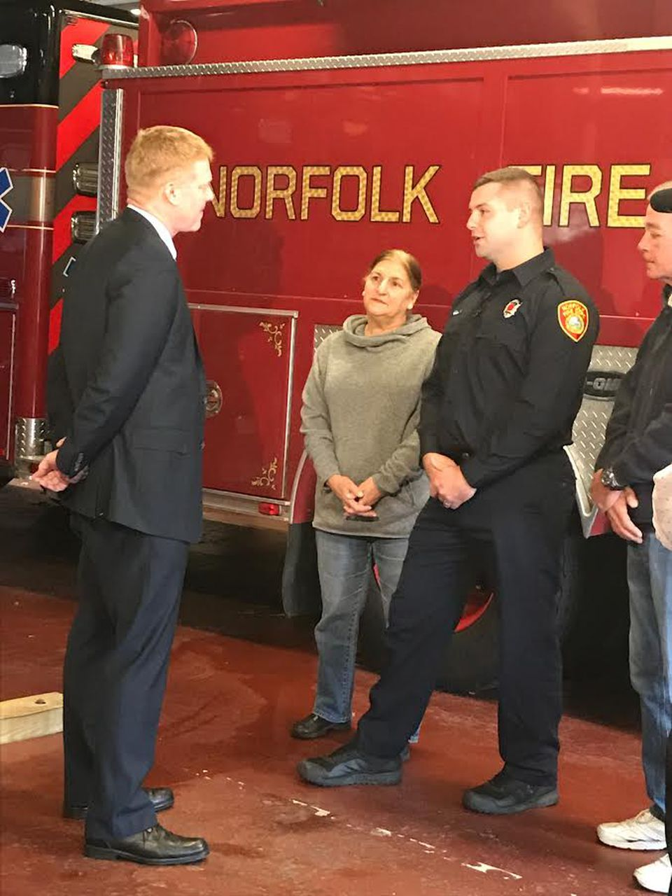Podsiadlo, left, and Brady, right with his parents, talk at the Norfolk fire department.