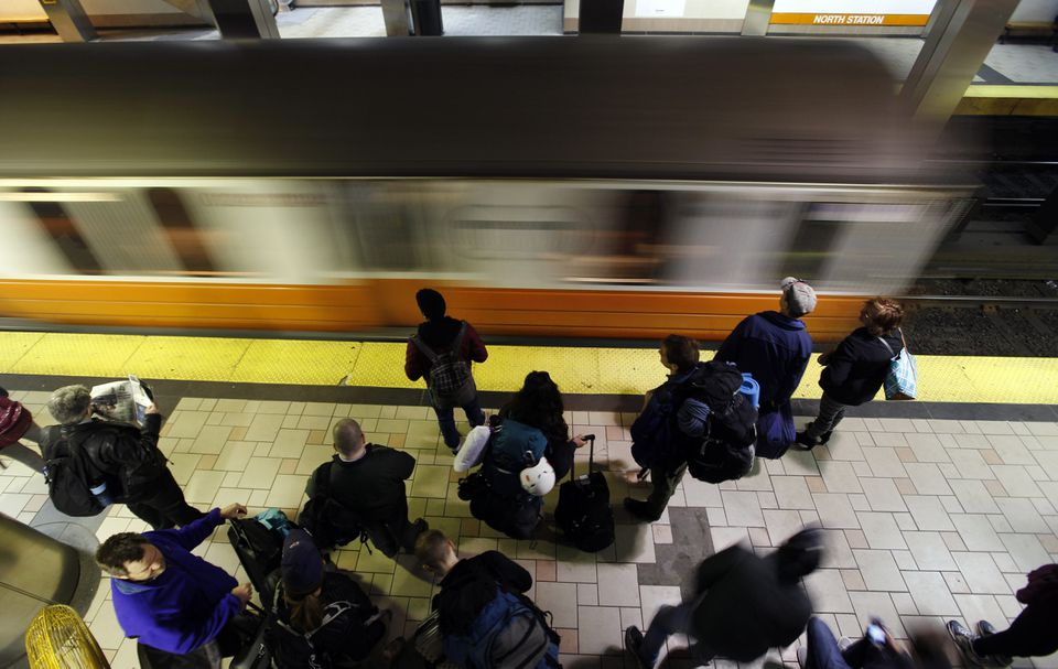 Passengers wait for an Orange Line train to pull in to North Station.