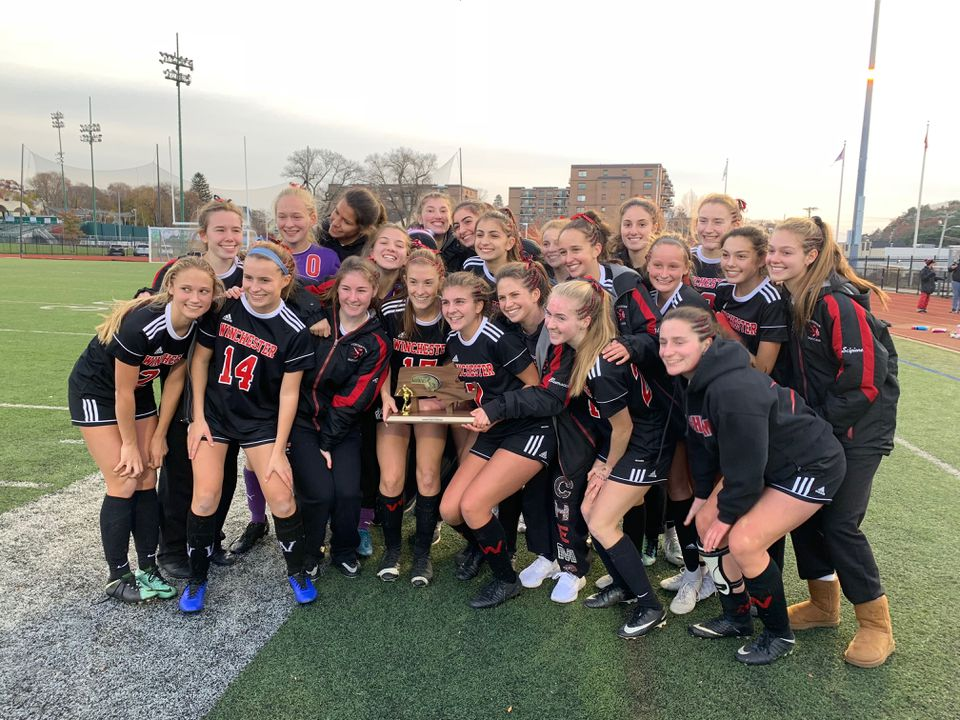 The Winchester girls' soccer team huddled with the hardware after their 3-1 win over Danvers for the Division 2 North title at Manning Field in Lynn.