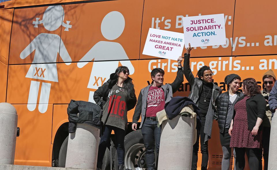 Protesters greeted a bus with anti-transgender messages in front of the State House.