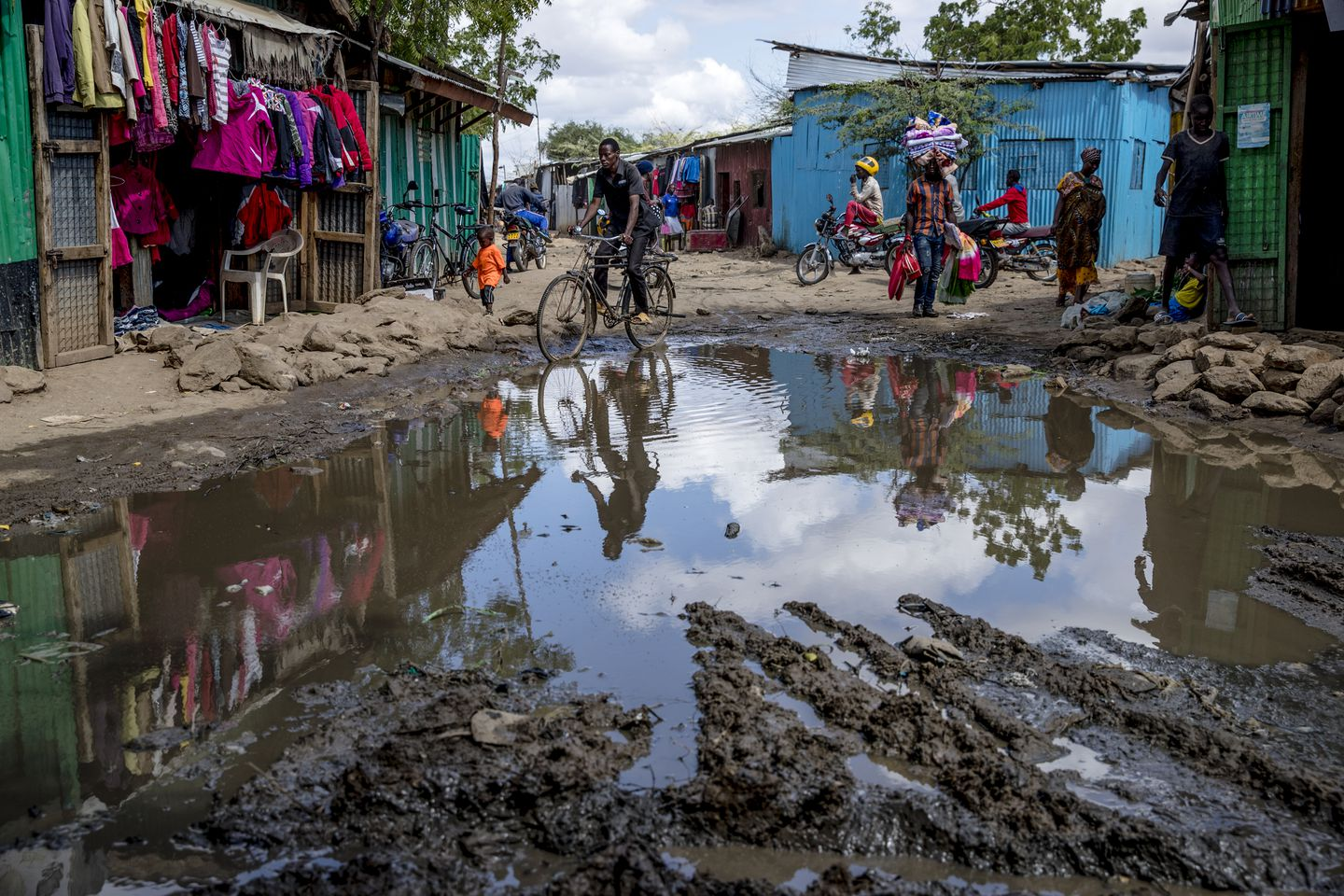 People made their way along a pool of standing water in the UNHCR refugee camp. Even after minor rains, water settles into pools that cause muddy and difficult conditions on roads.